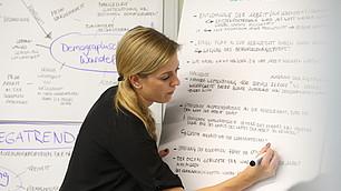 Die Moderatorin Carina Tschörner fixiert wesentliche Ergebnisse.